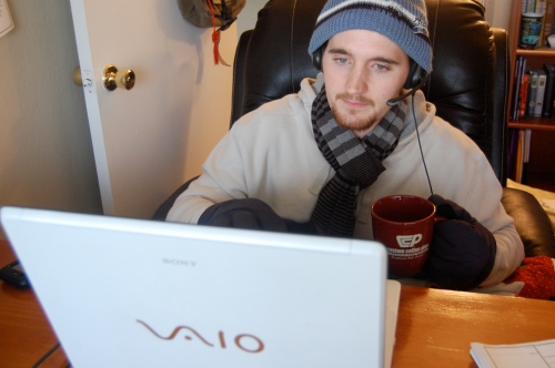 Makeshift office with computer, easy chair and coffee mug