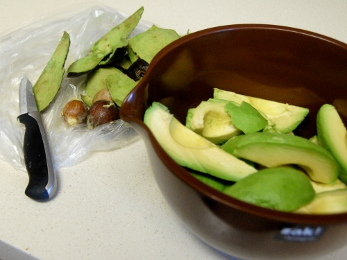 Bowl of sliced avocados next to the peel, seeds and knife
