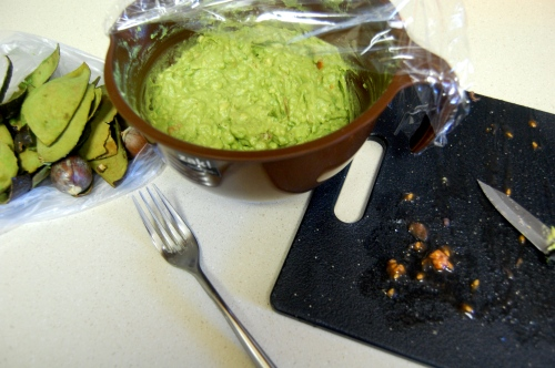 Bowl of guacamole next to cutting board, fork and skins
